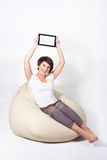 Young woman using iPad. Young woman sitting on sako and showing a tablet Royalty Free Stock Photography