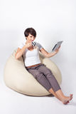 Young woman using iPad. Young woman sitting on sako with coffe and tablet Royalty Free Stock Image