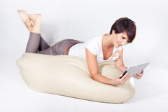 Young woman using iPad. Young woman lying on sako and using a tablet Stock Photography