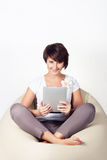 Young woman using iPad. Young woman lying on sako and using a tablet Royalty Free Stock Photo