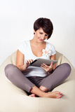Young woman using iPad. Young woman sitting on sako and using a tablet Royalty Free Stock Photo