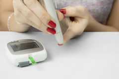 Young woman using a lancet. Hands of young woman using a lancet while examining blood sugar with a glucometer Royalty Free Stock Photography