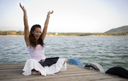 Young woman using a laptop. Happy young woman using a laptop on a pier Royalty Free Stock Image