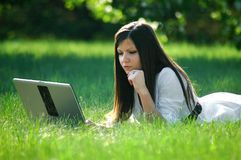 Young woman using laptop. In park Royalty Free Stock Image