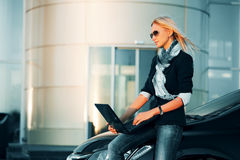 Young fashion business woman using laptop by car