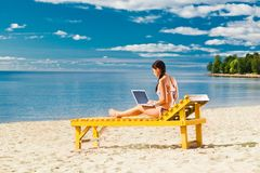 Young woman using laptop. On the beach Stock Image