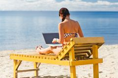 Young woman using laptop. On the beach Stock Photo