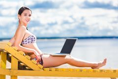 Young woman using laptop. On the beach Stock Photos