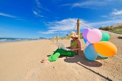 Young woman using laptop on the beach. Beautiful young woman with colorful balloons using laptop on the beach Royalty Free Stock Images