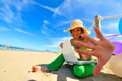 Young woman using laptop on the beach. Young woman with colorful balloons using laptop on the beach Stock Images