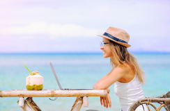 Young woman using laptop on the beach. Freelance work. Young woman with hat and coconut using laptop on the beach. Girl Freelancer working Royalty Free Stock Images