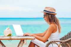 Young woman using laptop on the beach. Freelance work. Young woman with hat using laptop with empty white screen on the beach. Girl Freelancer working Stock Image