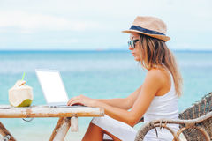 Young woman using laptop on the beach. Freelance work. Young woman with hat using laptop with empty white screen on the beach. Girl Freelancer working Stock Photography
