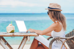 Young woman using laptop on the beach. Freelance work. Young sexy woman with hat using laptop with empty white screen on the beach. Girl Freelancer working Stock Images