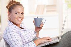 Young woman using laptop in bed drinking tea Stock Images