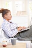 Young woman using laptop in bed at home Royalty Free Stock Photo
