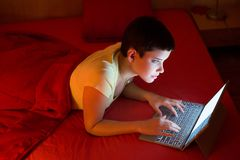 Young woman using laptop in bed Royalty Free Stock Image