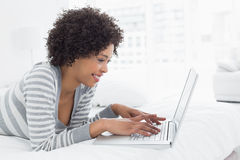 Young woman using laptop in bed Stock Photos