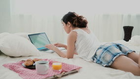 Young woman using laptop during breakfast lying on white bed at home. Brunette girl typing on pc computer. Royalty Free Stock Photos