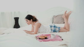Young woman using laptop during breakfast lying on white bed at home. Happy girl eat croissant and browses the Internet. Royalty Free Stock Image