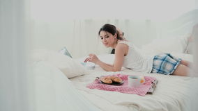 Young woman using laptop during breakfast lying on white bed at home. Happy girl eat croissant and browses the Internet. Stock Photo