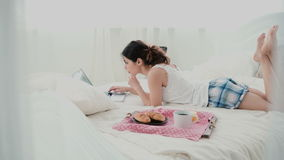 Young woman using laptop during breakfast lying on white bed at home. Happy girl eat croissant and browses the Internet. Royalty Free Stock Images