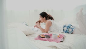 Young woman using laptop during breakfast lying on white bed at home. Happy girl eat croissant and browses the Internet. Royalty Free Stock Photos