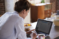 Young woman using laptop at breakfast, over shoulder view Stock Image