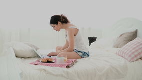 Young woman using laptop during breakfast sitting on white bed at home. Brunette girl typing message on pc, chatting. stock footage