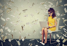 Young woman using a laptop building online business making money cash falling down Royalty Free Stock Image