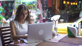 Young Woman Using Laptop In Cafe, Breakfast, Launch. Pretty female student with smile keyboarding something on notebook while relaxing after lectures in stock video
