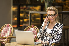 Young  woman using laptop at cafe. Royalty Free Stock Images