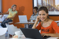 Young woman using laptop in cafe, smiling, portrait, couple in background Royalty Free Stock Photo