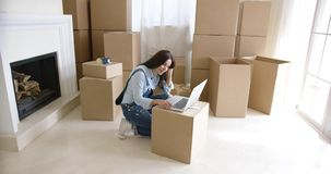 Young woman using a laptop on a cardboard box stock footage