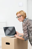 Young woman using a laptop on a cardboard box. As she catches up on news in her new home turning to smile at the camera Royalty Free Stock Photography