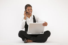 Young Woman Using Laptop and Cell Phone Royalty Free Stock Image