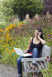 Young Woman Using Laptop and Cellphone in Park Stock Photo