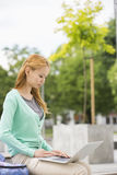 Young woman using laptop at college campus Royalty Free Stock Photos