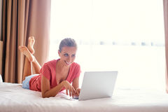 Young woman using laptop. Comfort working at home. Pretty young woman using laptop while laying on the bed Royalty Free Stock Image