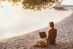 Young woman using laptop computer on a beach. Freelance work concept stock photography
