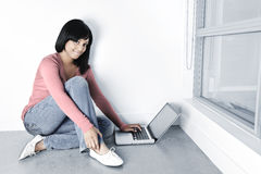 Young woman using laptop computer on floor Stock Photos
