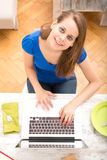 Young woman using a laptop computer after having breakfast Stock Image