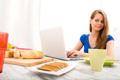 Young woman using a laptop computer after having breakfast Royalty Free Stock Images