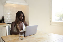 Young woman using laptop computer in her kitchen, close up Stock Image