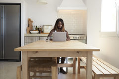 Young woman using laptop computer in her kitchen, front view Stock Images