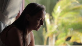 Young woman using laptop computer at home. Near the window with palm trees on the background stock video footage