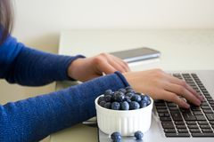 Young woman using laptop computer at home. And eating blueberry Stock Photography