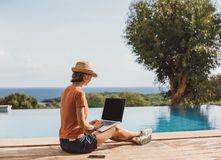 Young woman using laptop computer in hotel. Freelance work and travel concept. People using devices to plan trips, looking for hotels and flights, stay royalty free stock photography