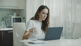 Woman using laptop computer at kitchen. Portrait of business woman watching news