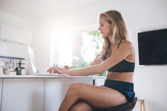 Young woman using laptop computer in the kitchen Royalty Free Stock Image